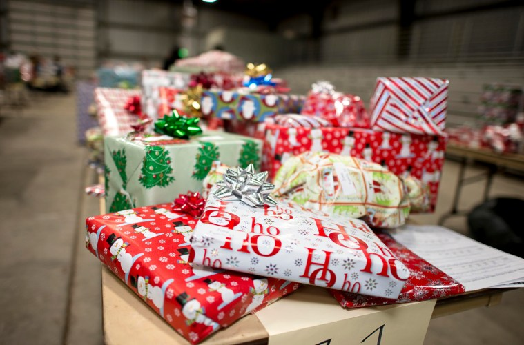 A stack of wrapped holiday gifts sits on a table.