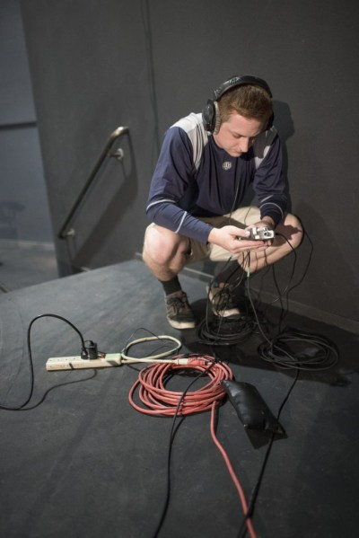 Kyle Bailey crouches over cords to set up audio equipment