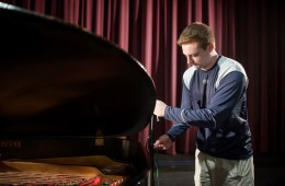 Kyle Bailey sets up audio equipment for a grand piano
