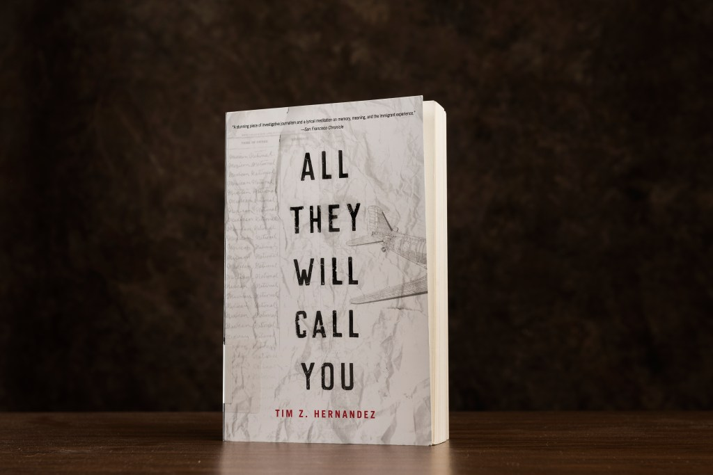 """The book """"All They Will Call You,"""" with a white cover, is silhouetted against a black background"""