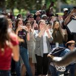 Clapping people holding up cell phone cameras