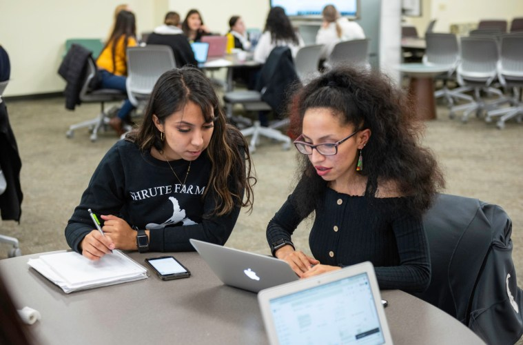 Students sit at a table with a laptop, cell phone, and notebook to work on a presentation.