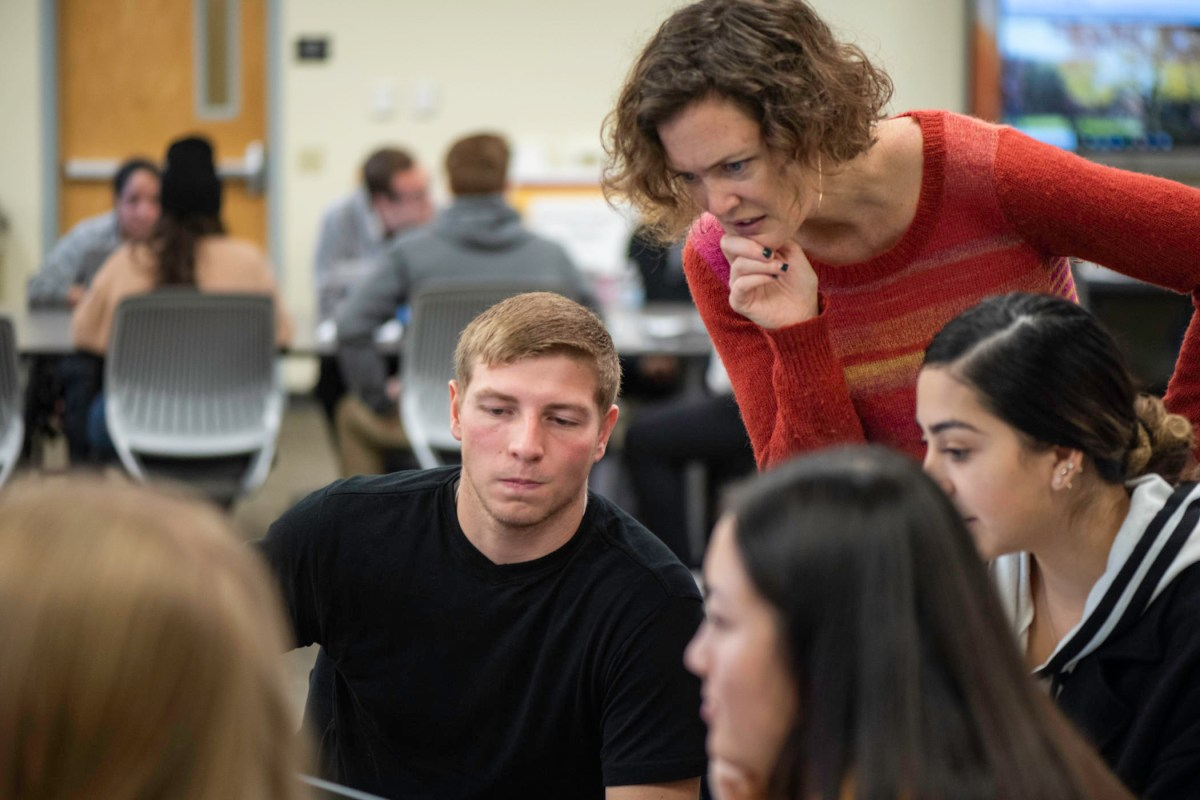 Students look at a computer screen with a teacher leaning over behind them.