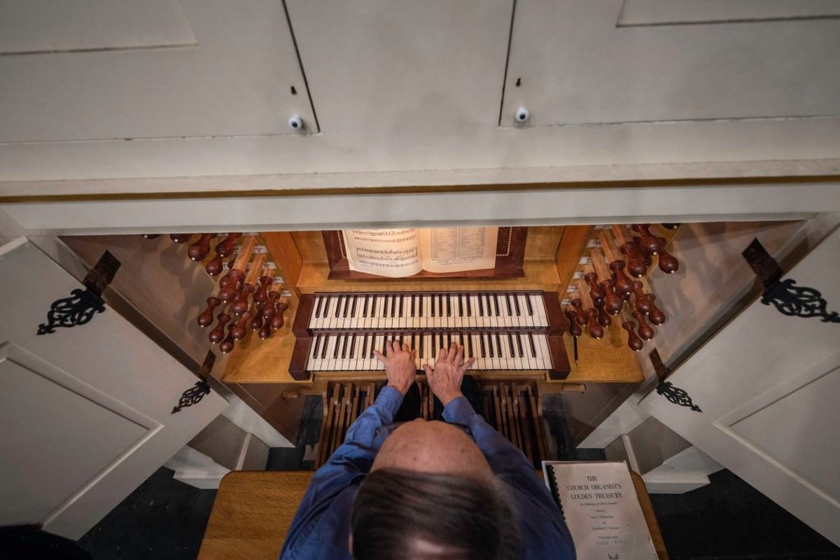 An overhead view of a man playing the organ keyboard.