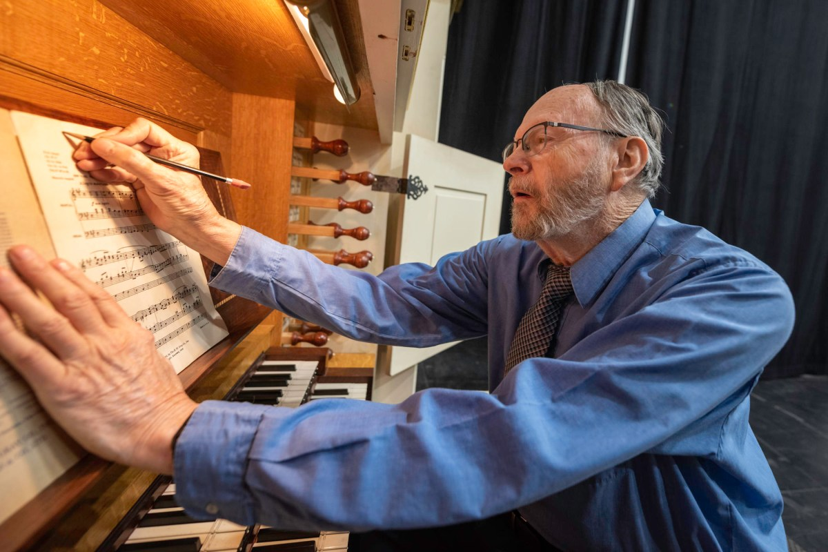 David Rothe makes notes on a sheet of music while seated at the organ keyboard.