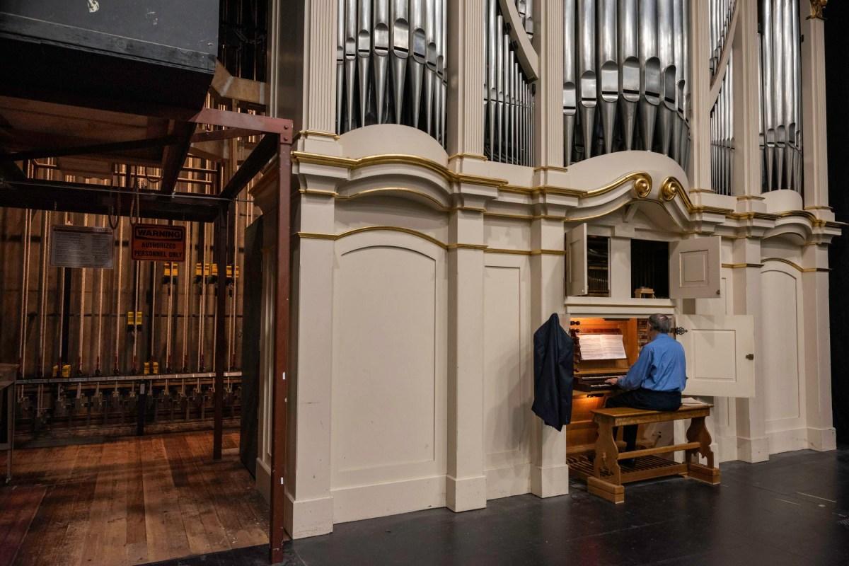A man sits at the organ keyboard and plays