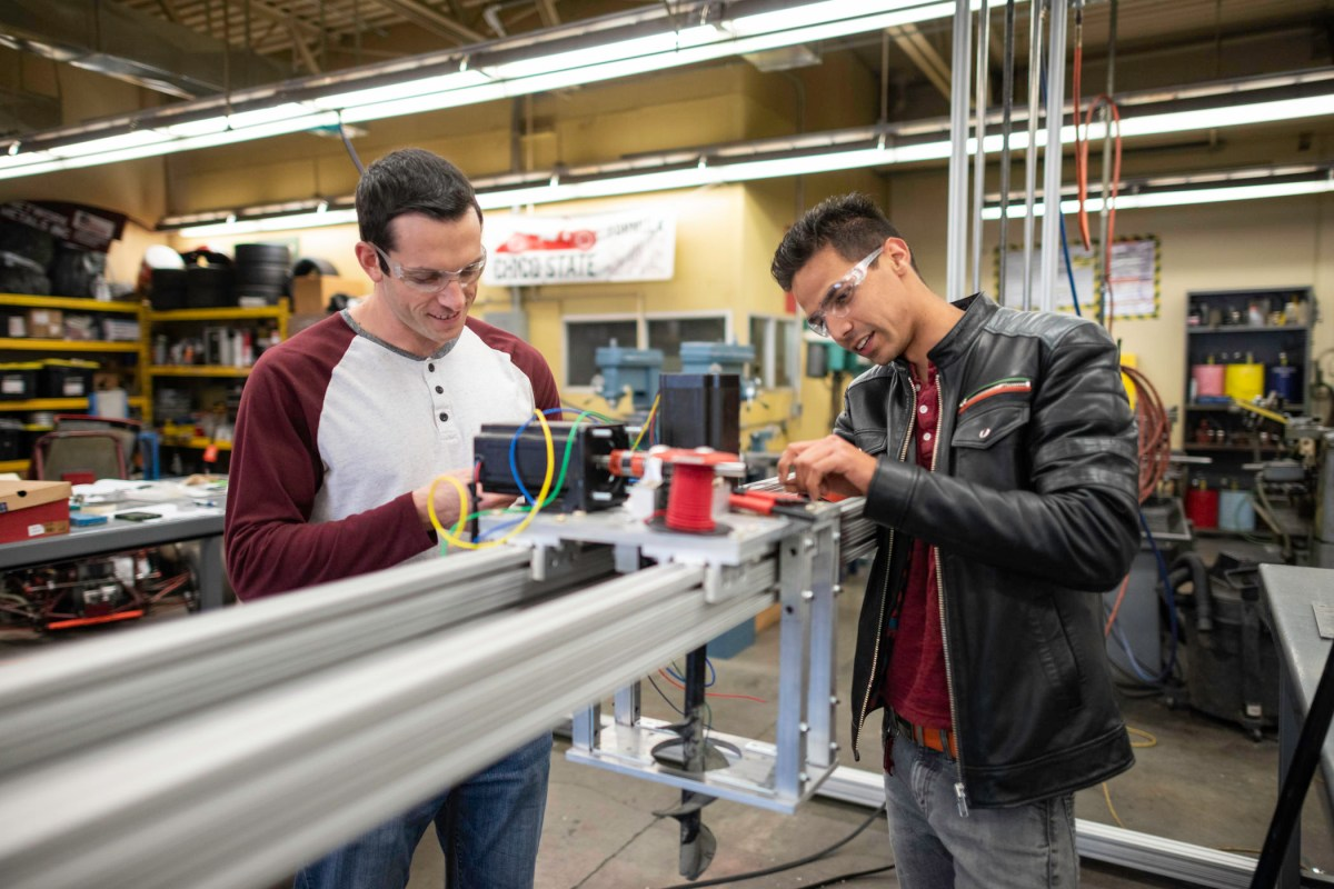 Two students work on their large-scale 3-D printer that will build homes out of concrete.