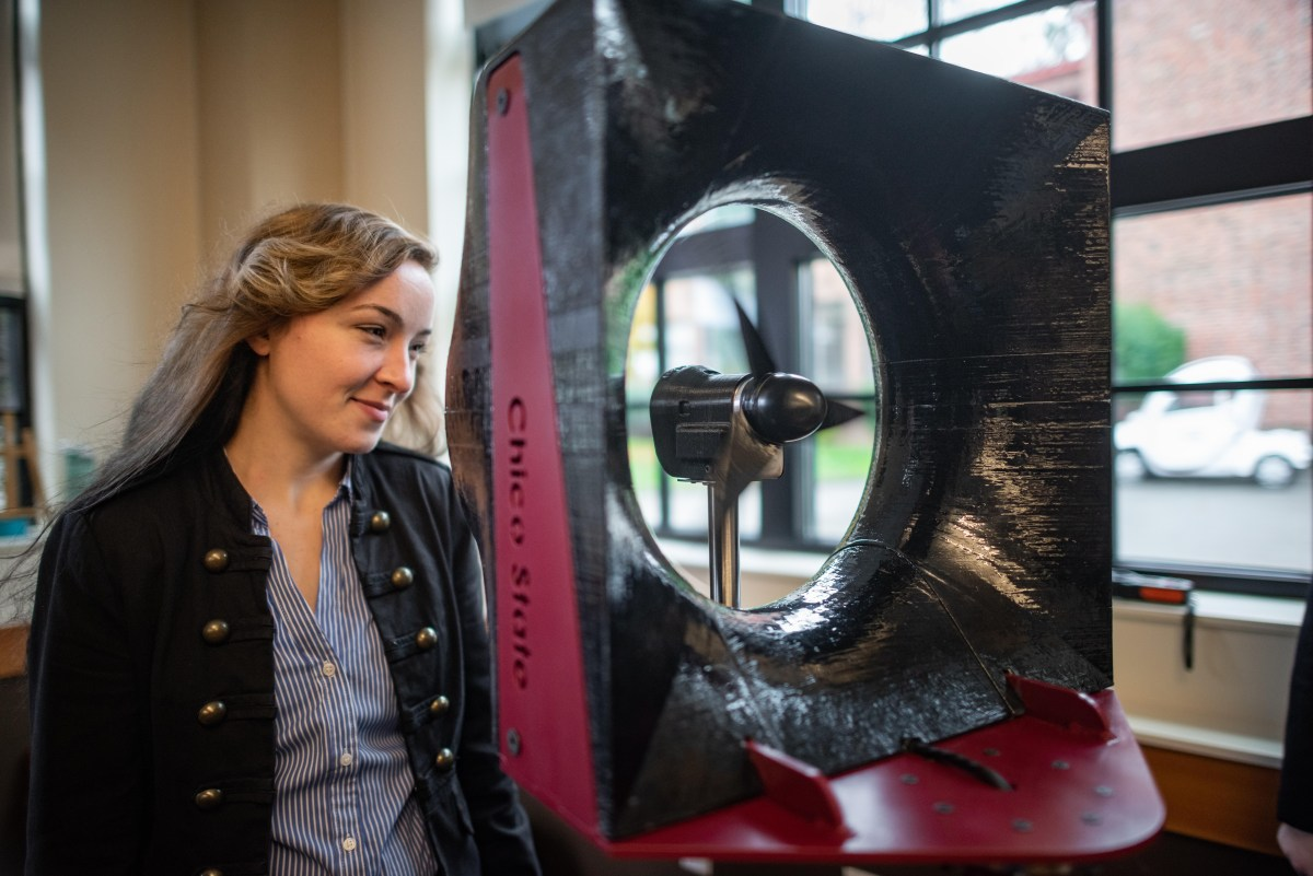 Kate Gordon looks into a wind tunnel as it blows her hair back.