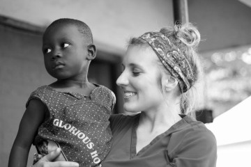 A student holds a young child in her arms at the Kristina Chesterman Memorial Clinic.