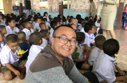 Pengcheng sits on the floor of a classroom surrounded by small children in uniform.