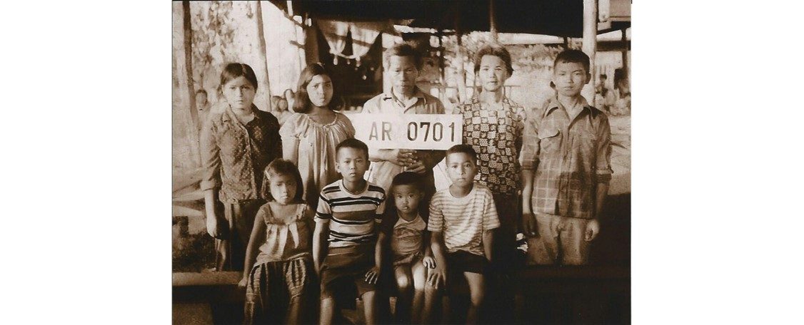 Neil and his family pose for a photo at a refugee camp in Thailand.