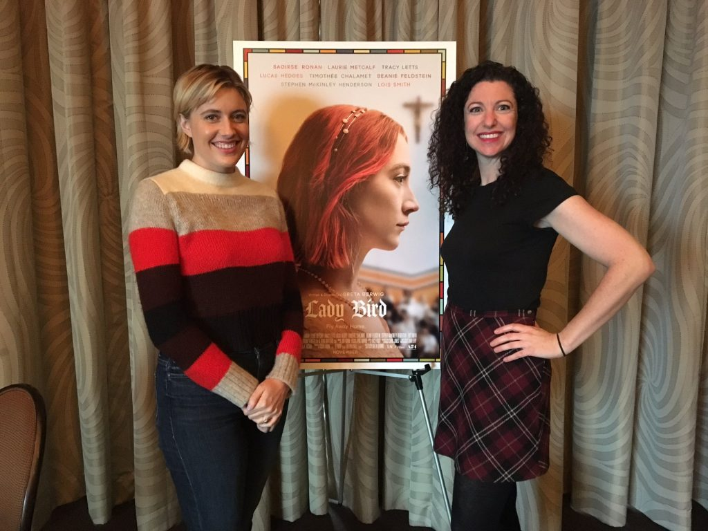 Rachel Belle poses with film director Greta Gerwig in front of a poster for the film Lady Bird.