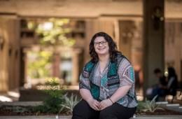 Elizabeth Konecny sits for a posed photo on a planter box by Meriam Library.