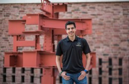 Jason Alhumaidi stands in front of a sculpture of steel in front of Langdon Hall.