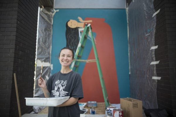 Autumn Robertson smiles, holding a paint tray, in front of a mural of a woman.