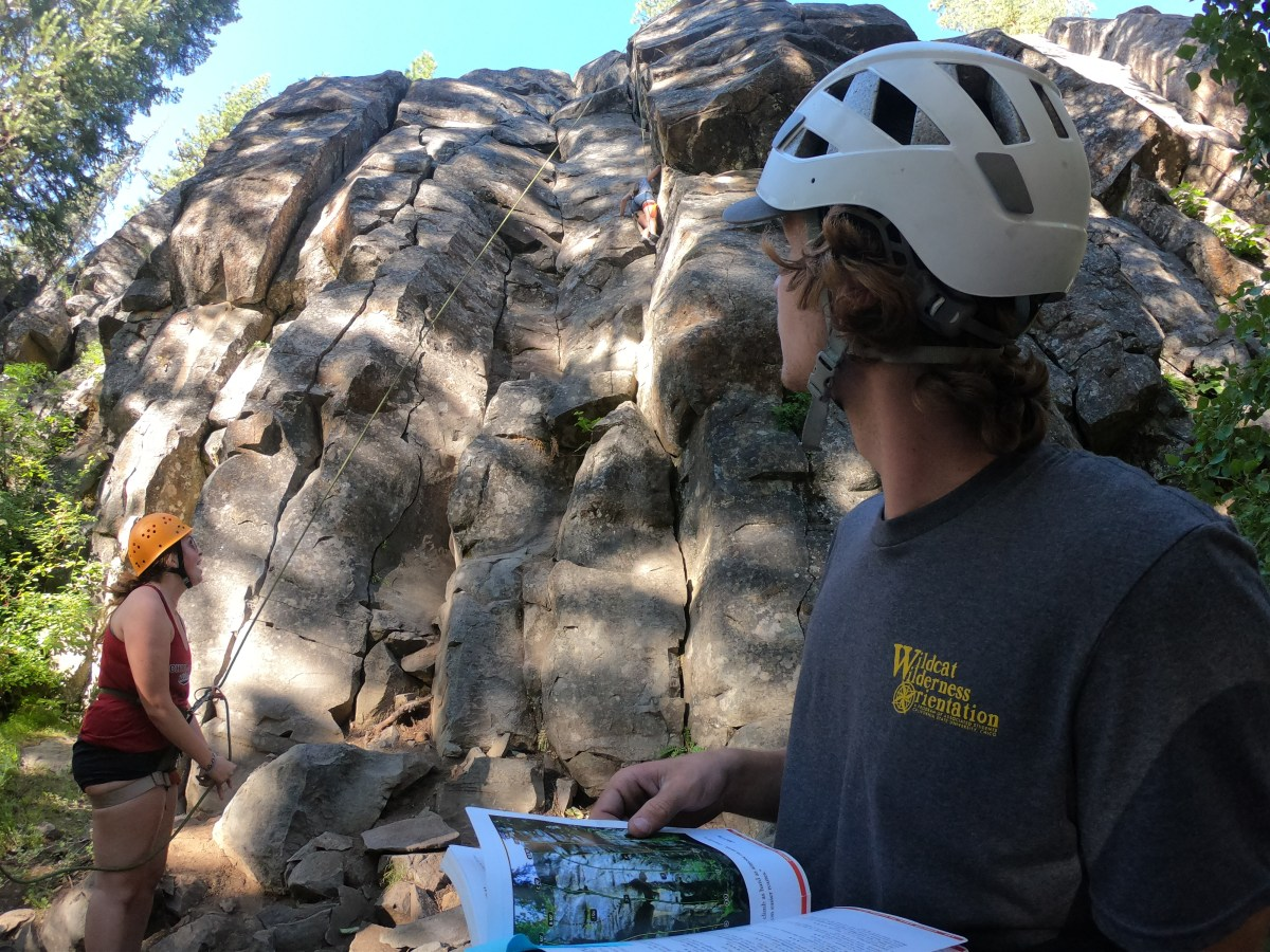 A student reads a guide book on rock climbing as students wearing helmets ascend a rock wall behind him.