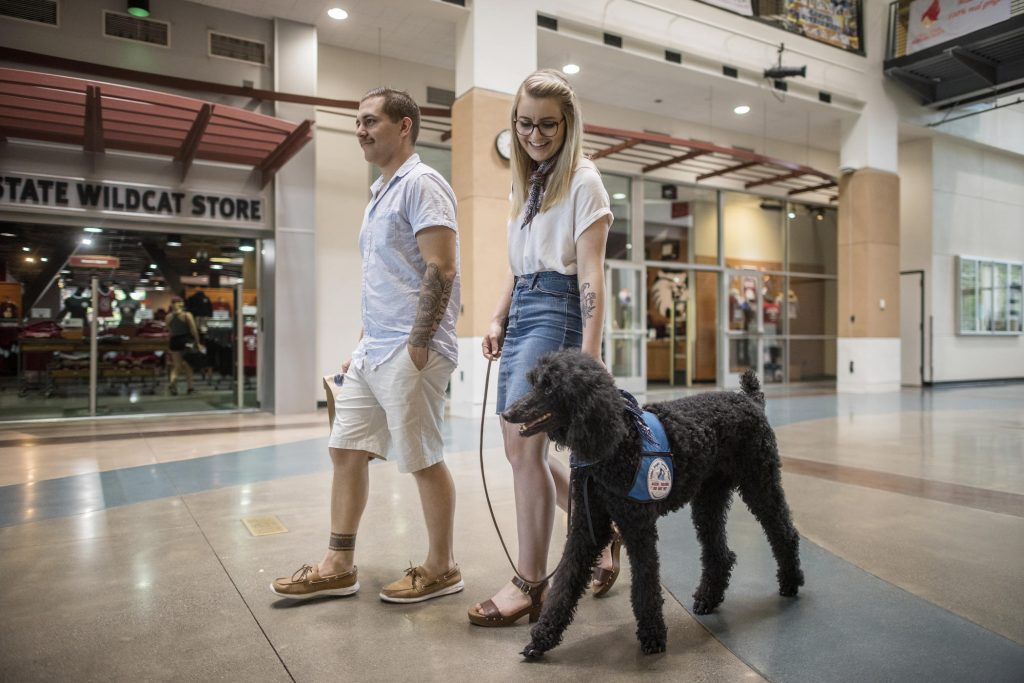 Distance learning student Taylor Coutts (center), along with her husband, Michael, and service dog, Davy, visited the Chico State campus for the first time in May, just days before she received her degree in sociology.