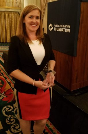 Ashley Casey holds the Women to Watch Emerging Leader Award in a posed picture.