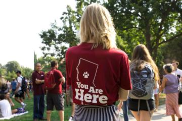"""Back of a student whose t-shirt shows a map of California with a paw print on Chico and reads """"You Are Here"""""""