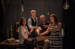 a group of four faculty gather around a lit lightbulb