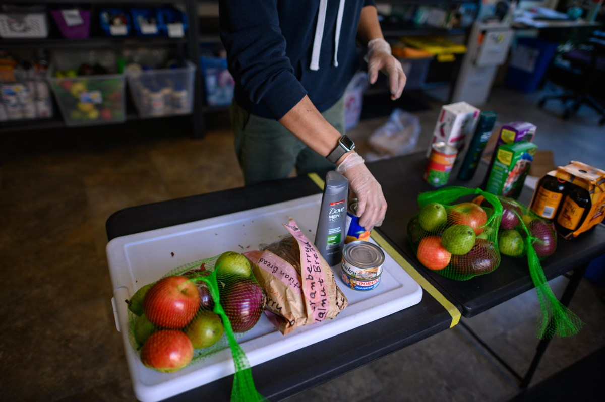 A gloved hand reaches into a collection of fresh and packaged food and hygiene items.