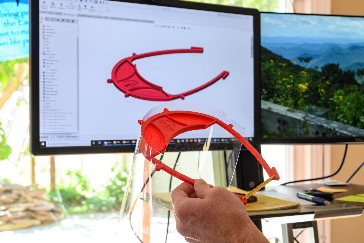 a hand holds up a 3D printed mask against a model on a computer screen.
