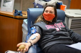 Anna Paladini smiles behind a mask as she gives blood.