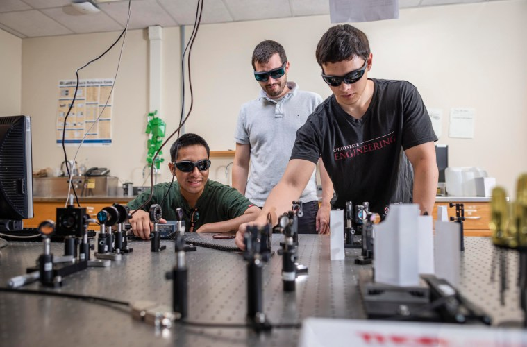 Three men in protective eyewear do laser testing over a table.