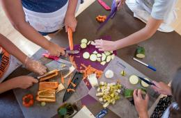 Overhead view of children chopping vegetables on cutting boards