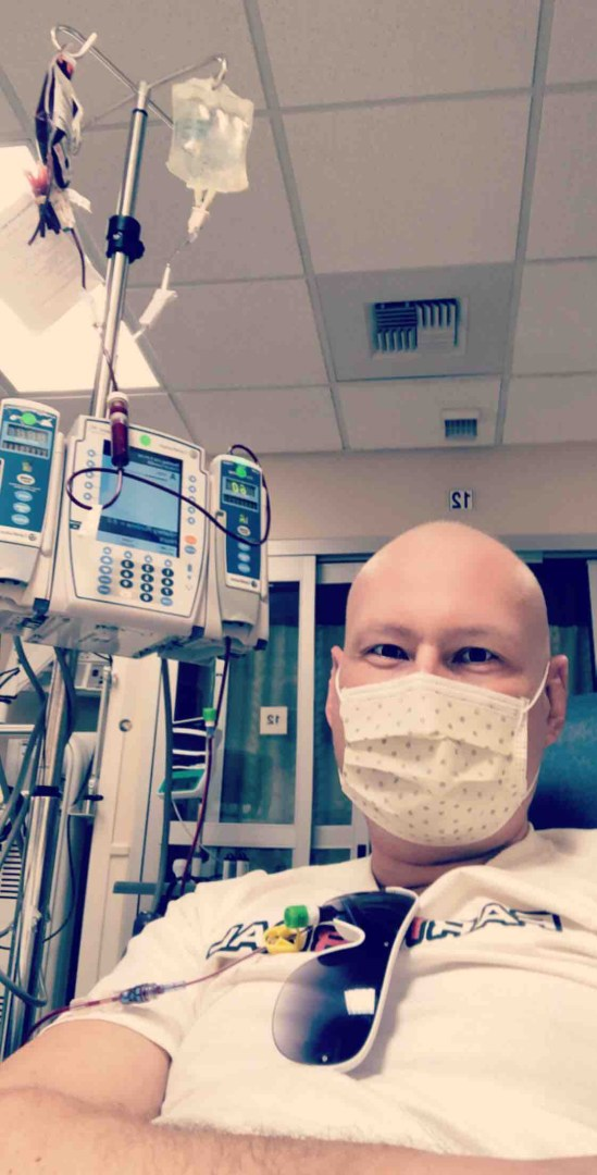 Slade Giles wears a mask while connected to tubes at a chemotherapy appointment.