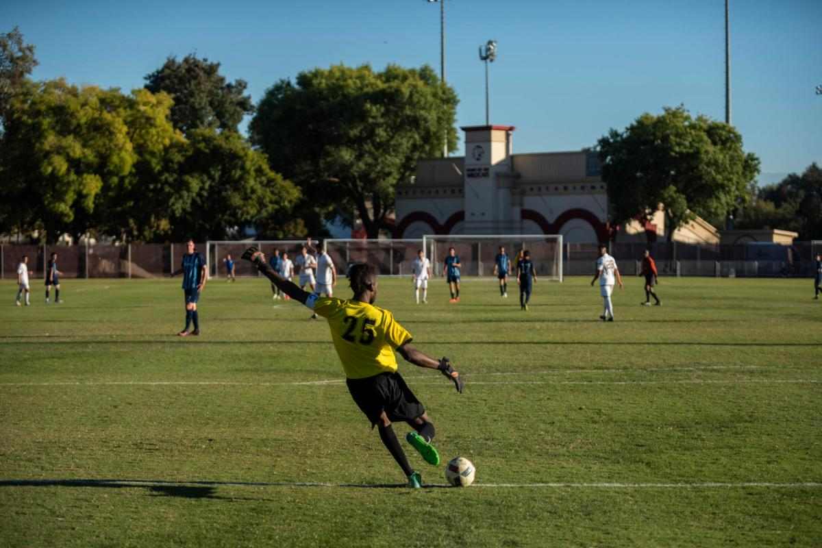 Chico State goalkeeper Damion Lewis sends a goal kick as his teammates await.