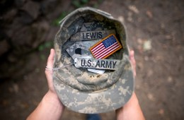 "Two hands hold an Army cap, which contains two dog tags, an American flag patch, and tags reading ""Lewis"" and ""U.S. Army."""
