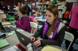 Kallie Griffin types on a laptop in the medical command center, a wall of medical supplies behind her.