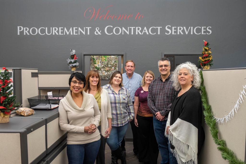 Procurement staff pose for a group portrait in their office.