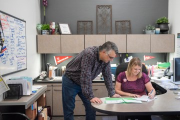 Michael McNairn and Sara Rumiano huddle over a desk while reviewing paperwork in the Procurement office at Chico State.