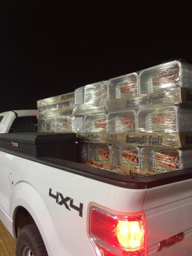 A pallet of aluminum foil pans sits in the back of a truck at night.