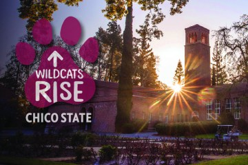 The Wildcats Rise logo is seen over a sunrise behind Trinity Hall.
