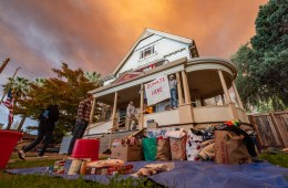"""Piles of donated goods sit on the lawn in front of the Phi Kappa Tau house, with a sign reading """"Donate here."""""""
