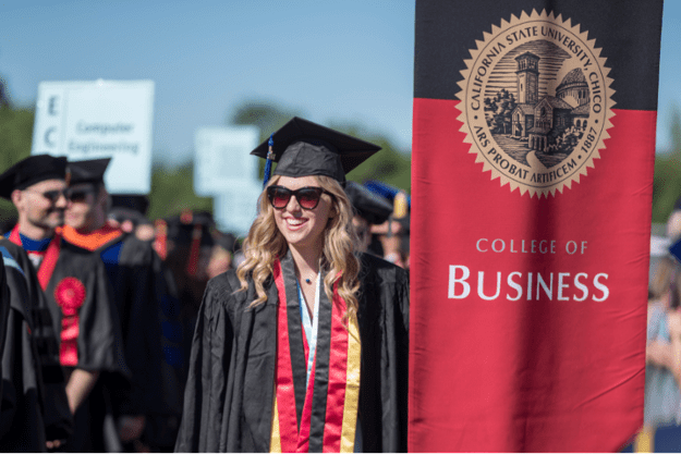 A college of Business graduate poses in cap and gown.
