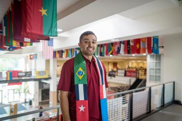 Marco Macotela stands on the second floor of the BMU with flags from around the world behind him.