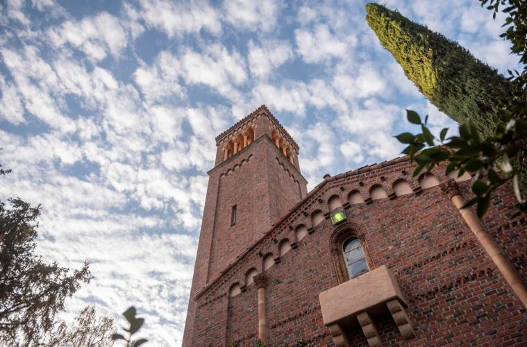 The bell tower of Trinity Hall rises into the clouds on a beautiful fall morning on the Chico State campus.