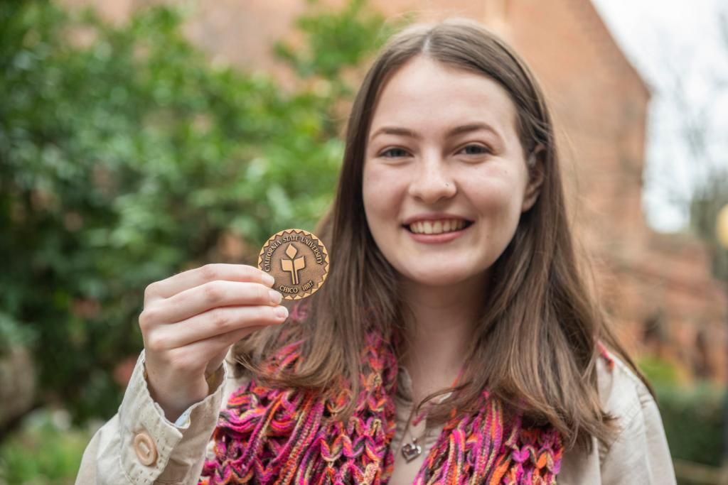 Emily Zarback holds the Presidential Medallion she received from Chico State President Gayle Hutchinson.