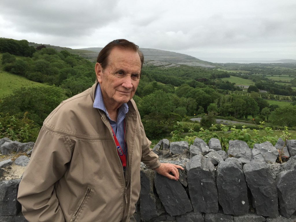 Al Brown stands at a rock wall with sprawling hillsides behind him.