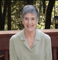 Portrait of Linda Henderson sitting on a bench.