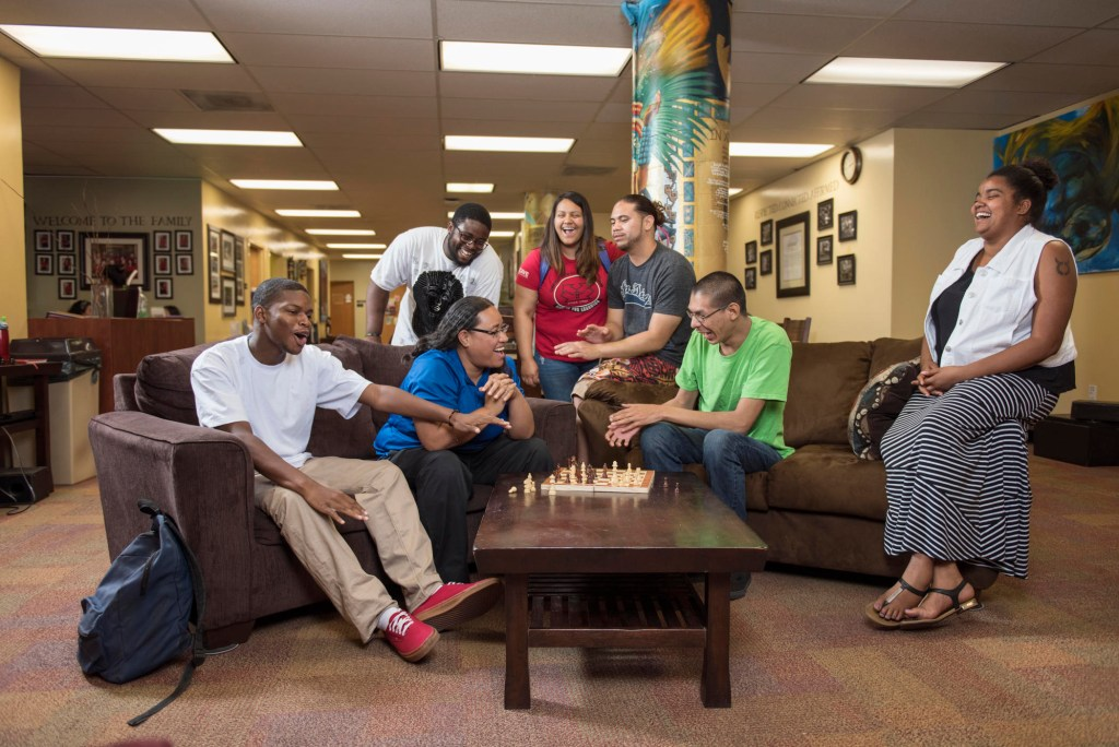 A group of students gather on couches in the CCLC and play chess on the coffee table.