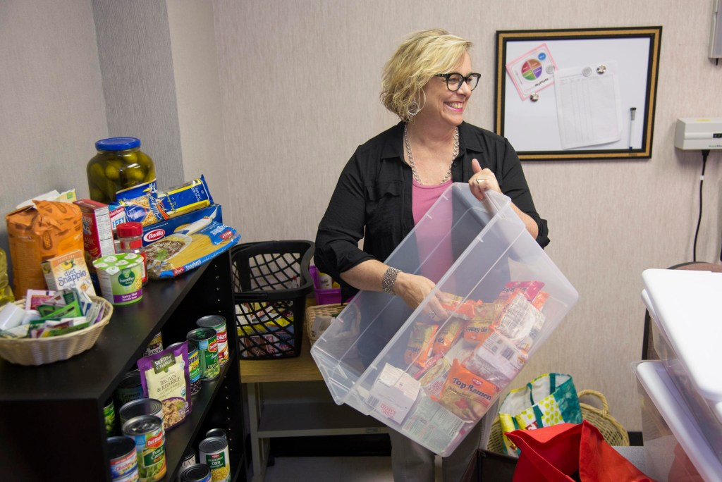 Kathleen Moroney stocks the shelves of the Hungry Wildcat Food Pantry.