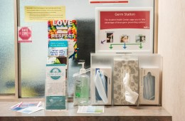 Information pamphlets, hand sanitizer, and boxes of face masks and issues sit on a counter.