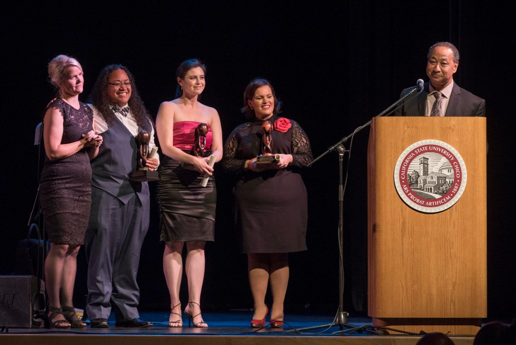 Katie Peterson, Krystle Tonga, Amy Hormann, and Erica Flores stand on stage at the CCLC's Open House and Gala to receive an advocate recognition from Carter.