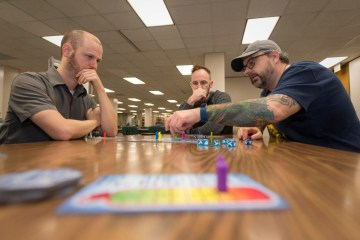 Three campus faculty and students playing the game Dicey Peaks.