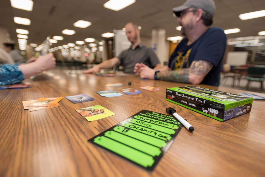 Image of game pieces on a table with players talking in the background.